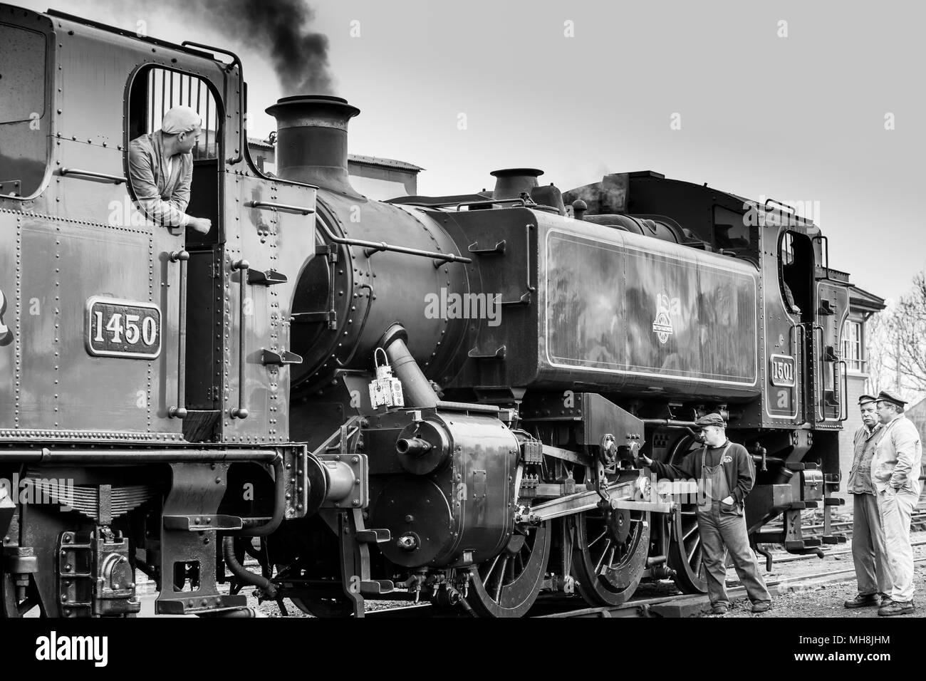 Preserved steam engines on Severn Valley Railway heritage line awaiting departure. Black & white landscape image reflecting nostalgia of bygone era. - Stock Image