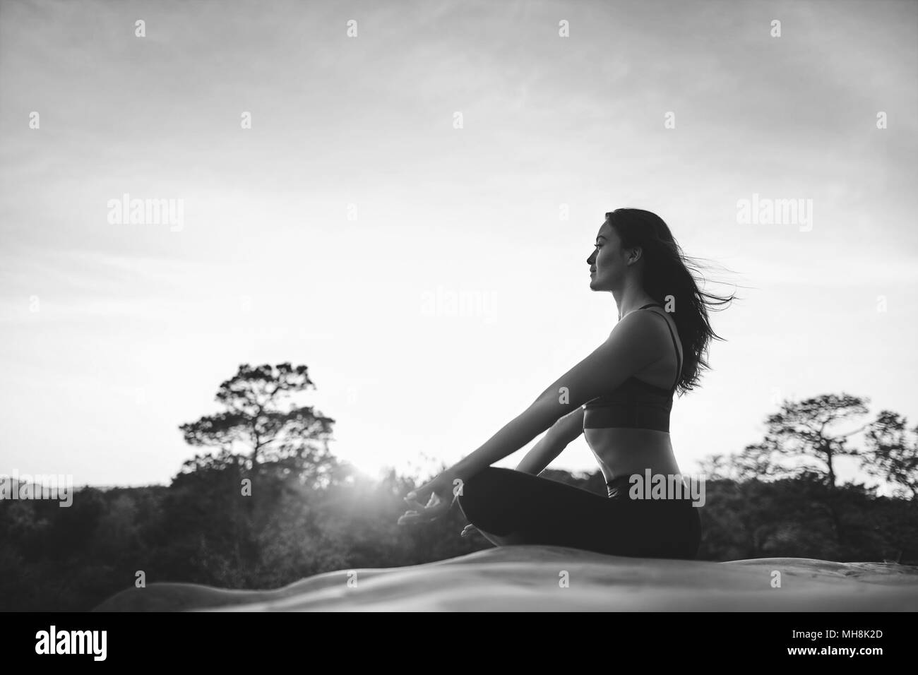 Young woman practicing yoga outdoors - Stock Image