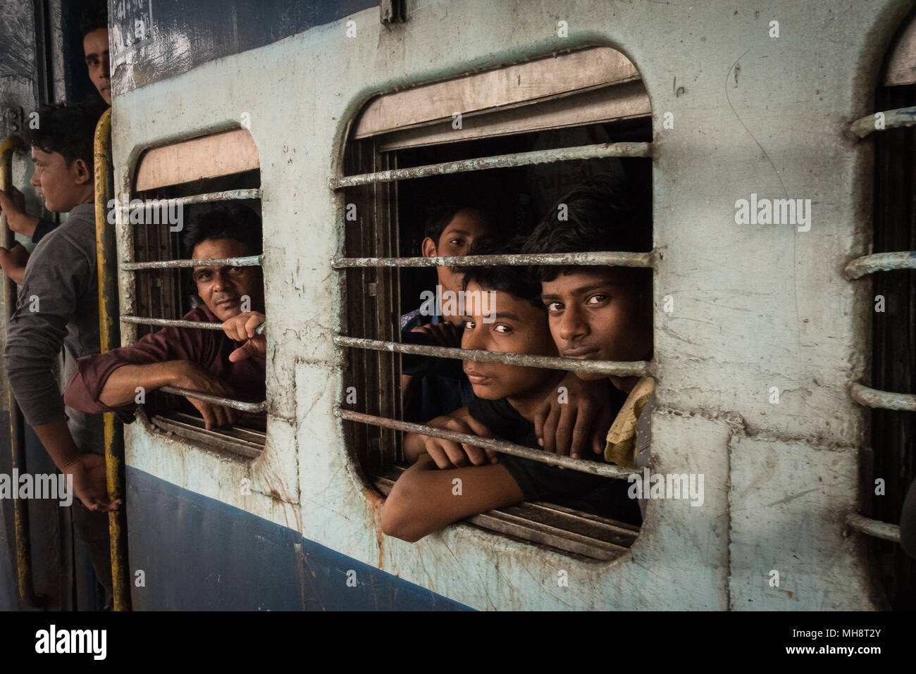 Men sitting in a second class rail car just as it is pulling out of the station in Sonepur, India. - Stock Image