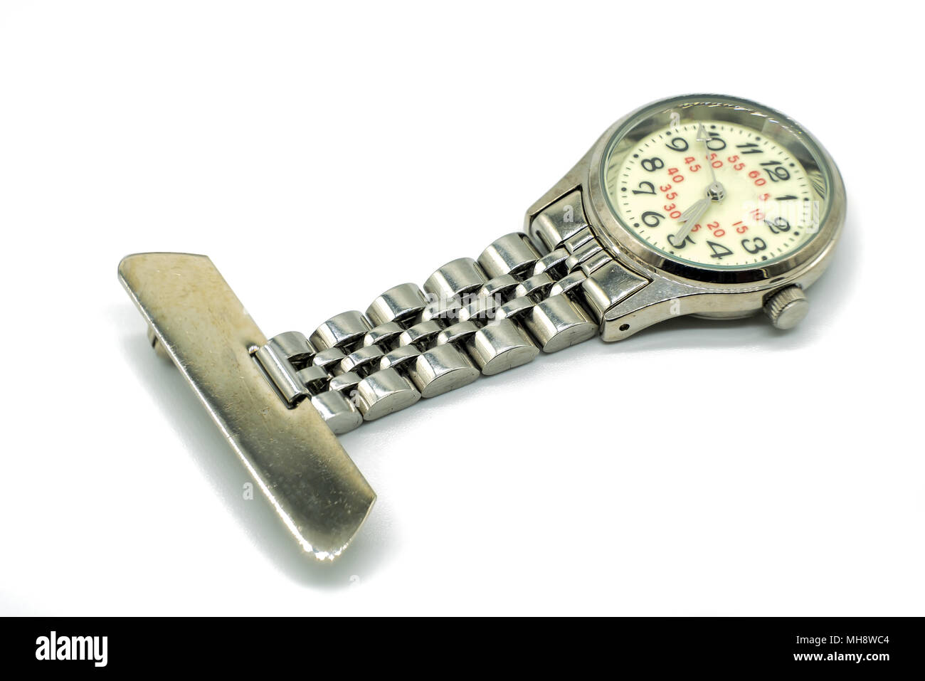 An old nurses silver clasp watch isolated on white background. The face of the watch is blurred due to age and usage. - Stock Image