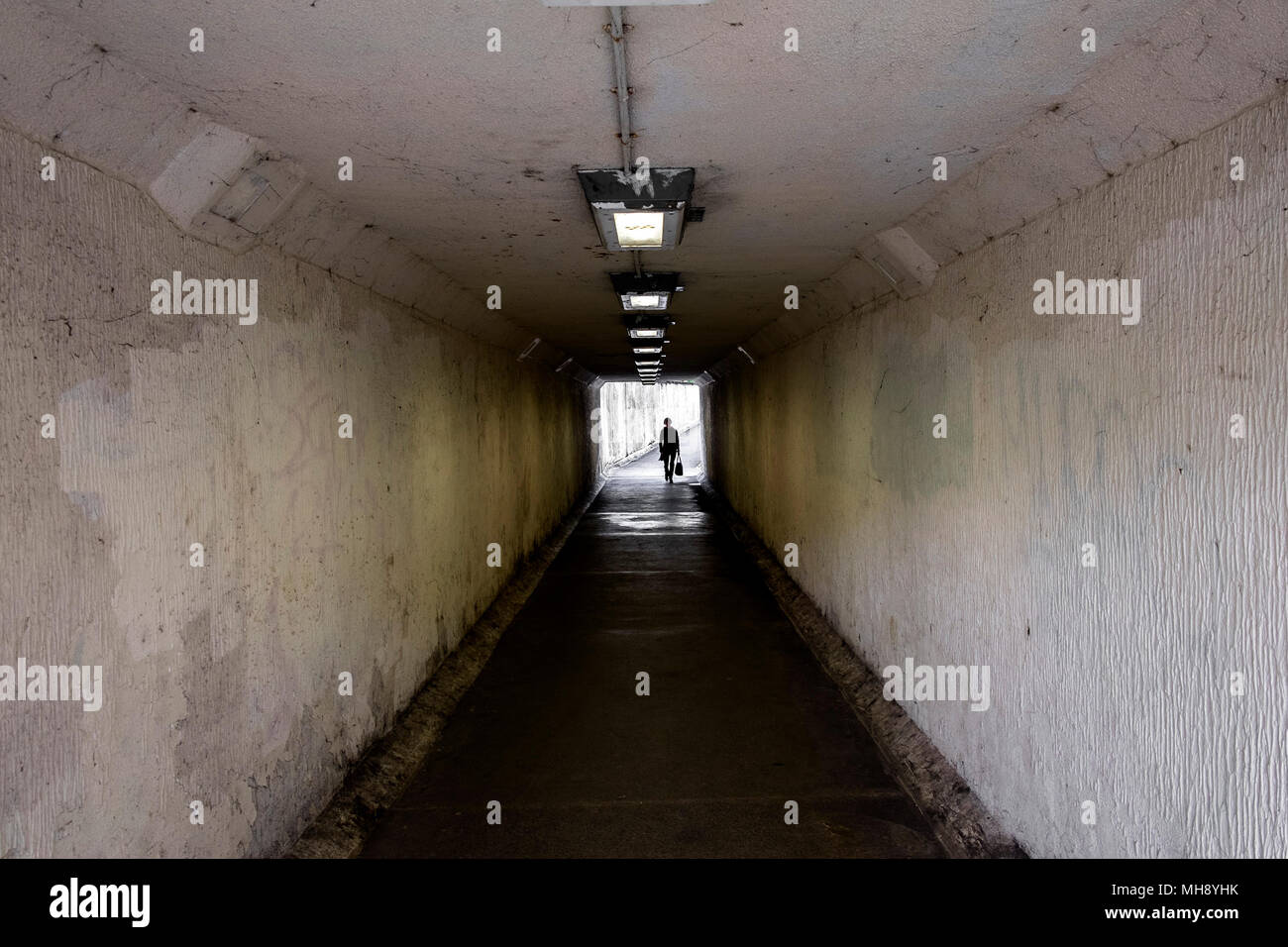 A figure walking through a dark and gloomy underpass in truro City centre in Cornwall. - Stock Image