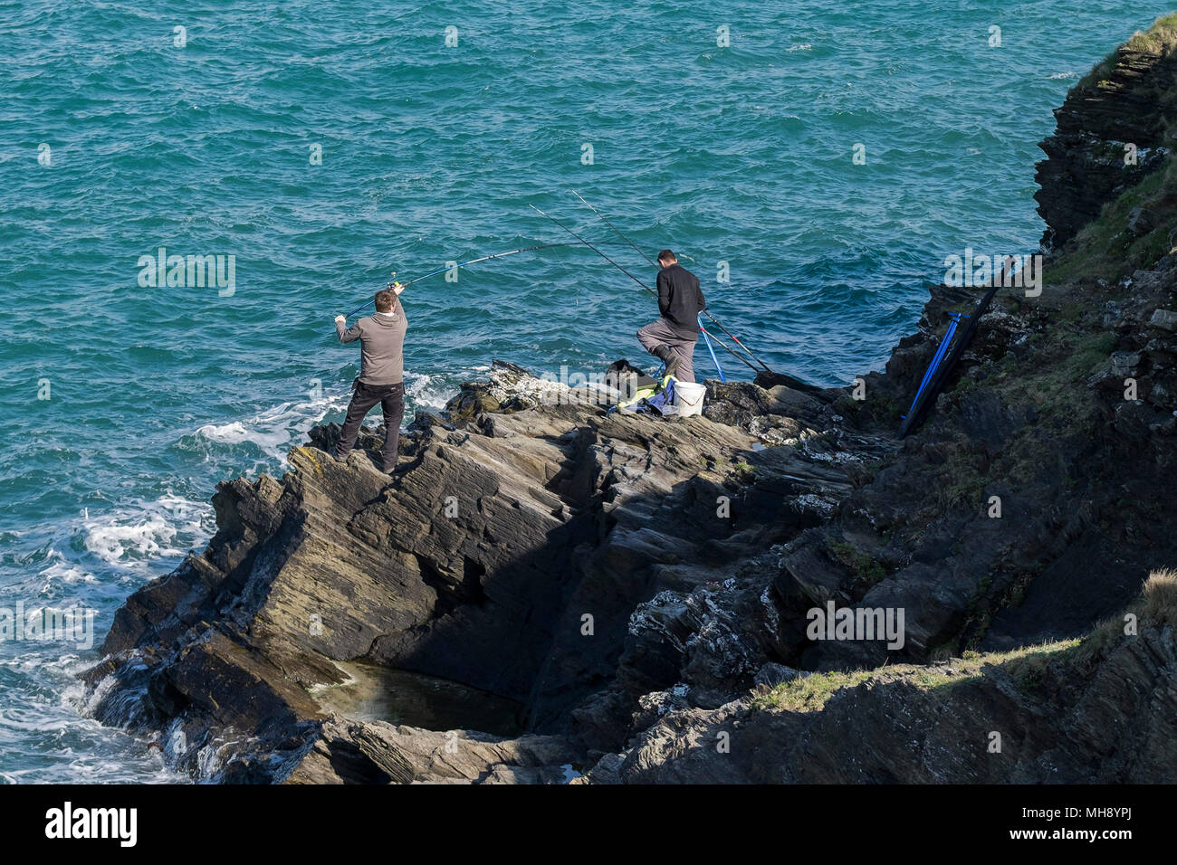 Anglers fishing off rocks in Newquay in Cornwall. Stock Photo