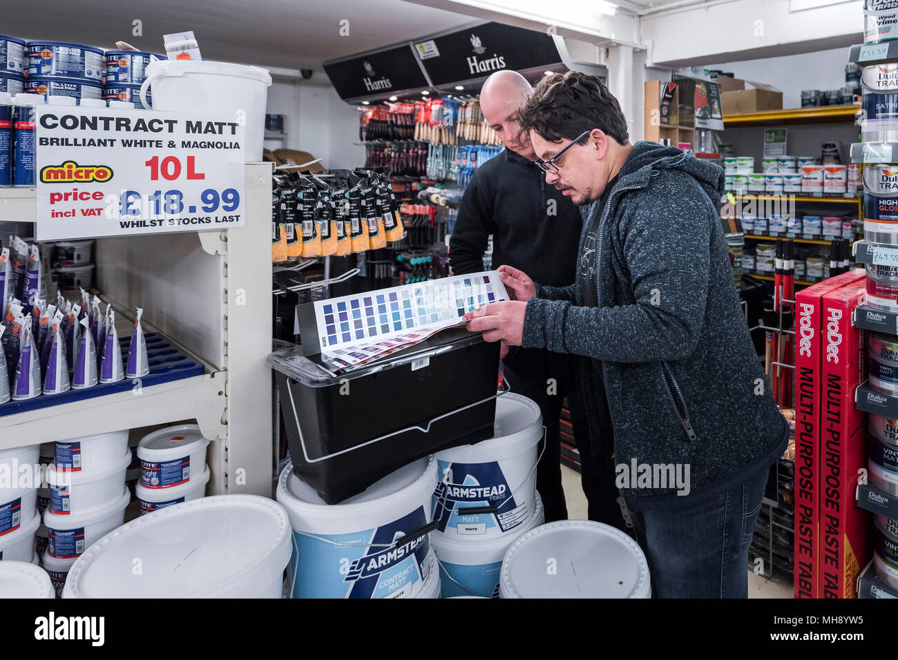 A staff member advising a customer in a DIY shop. - Stock Image