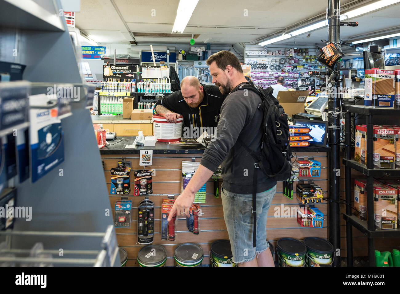 A customer asking a question in a DIY shop. - Stock Image