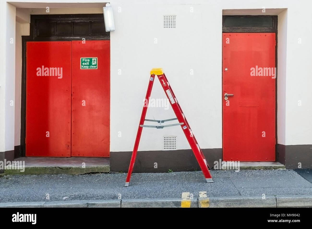 A red step ladder in between two red doors. - Stock Image