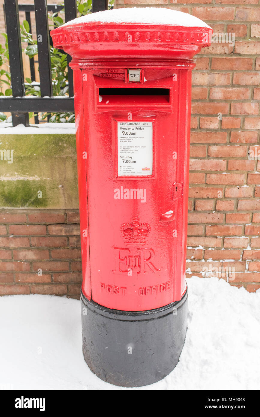 A traditional red pillar post box standing in the snow in Newcastle, Tyne and Wear, England, GB. - Stock Image