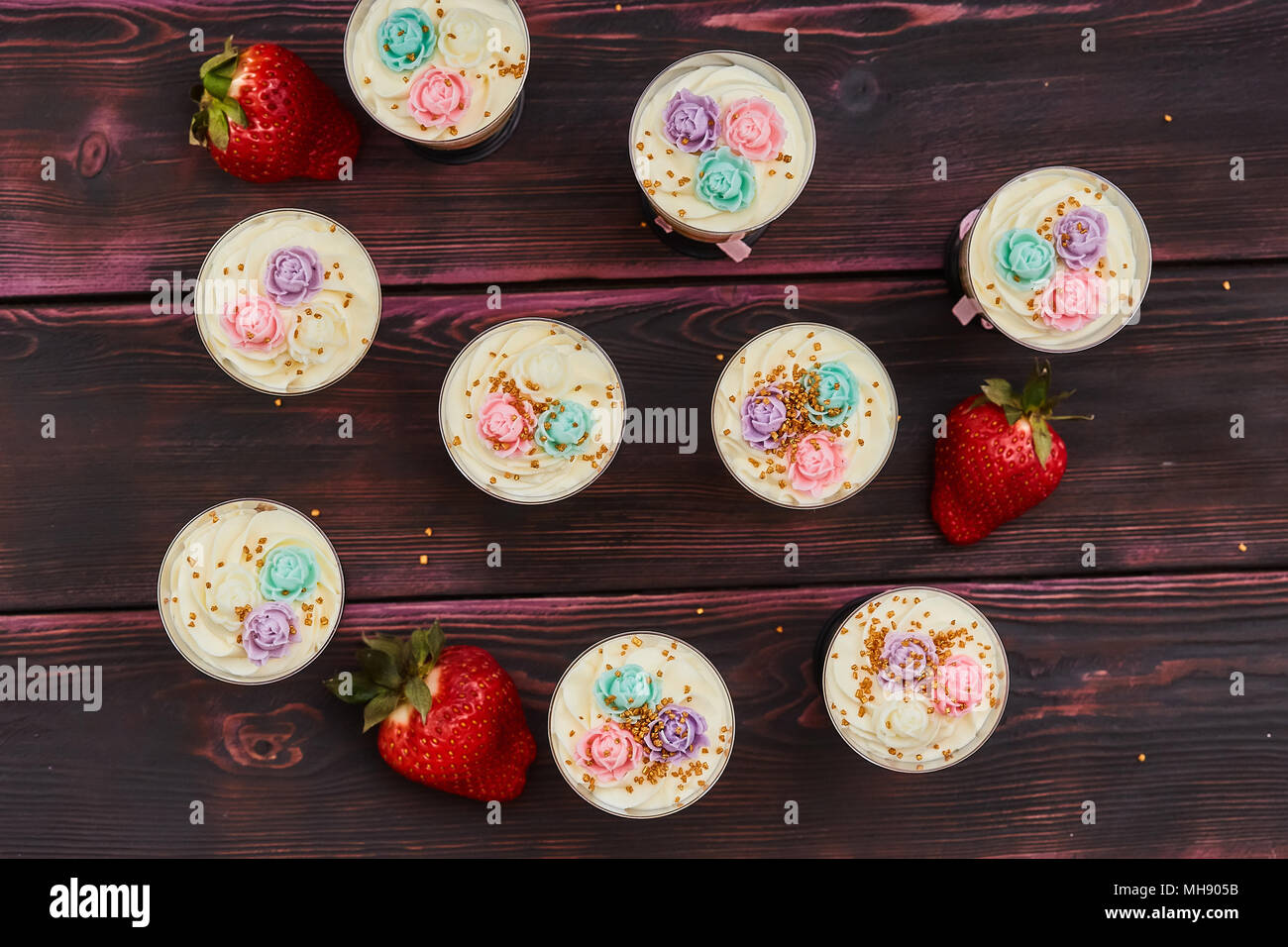 Cake with strawberry served in glass shots, wooden background - Stock Image