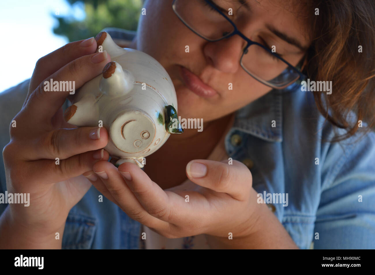 Millennial woman holding a ceramic piggy bank, looking despondent, close-up - Stock Image