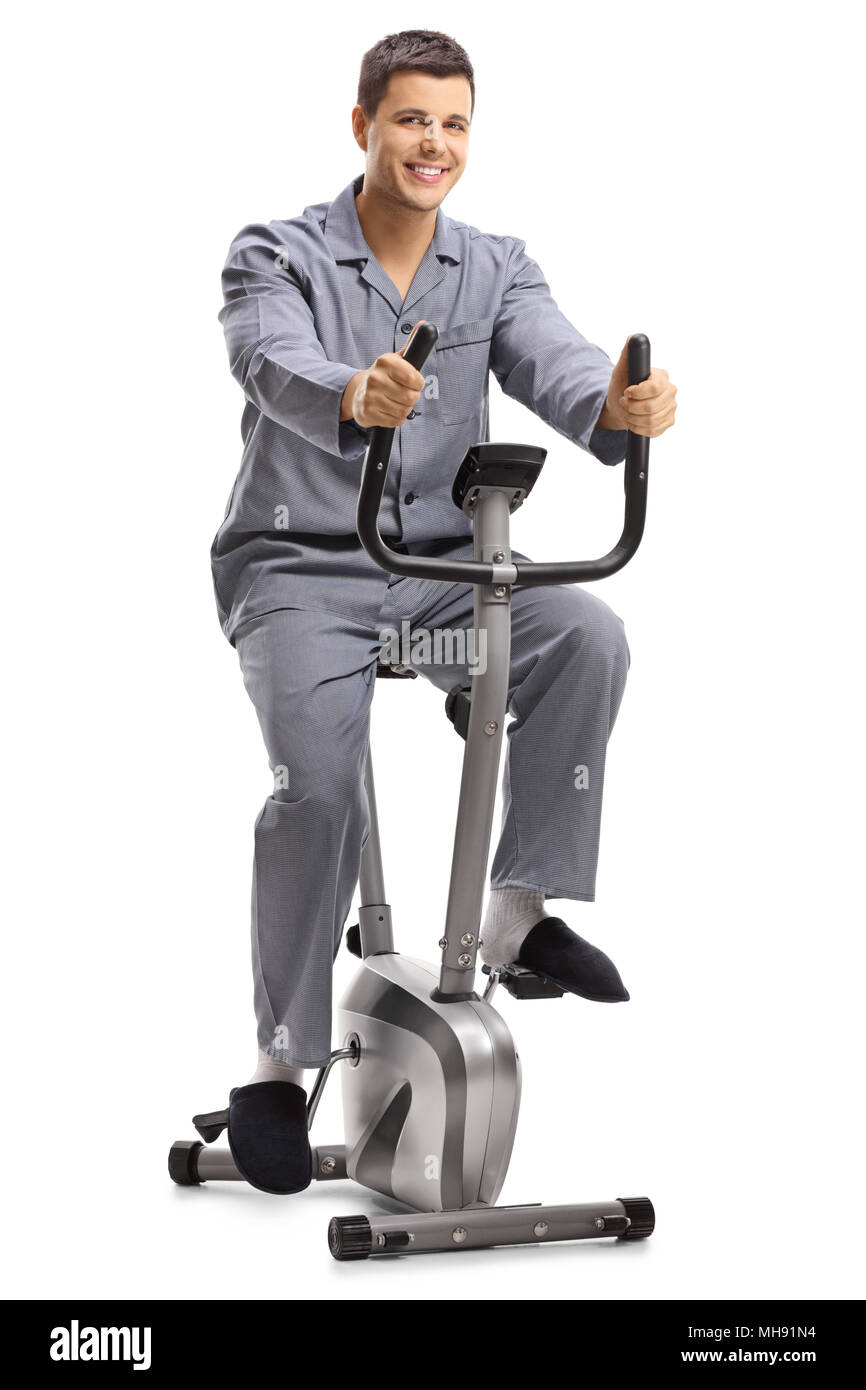 Young guy in pajamas exercising on a stationary bike isolated on white background - Stock Image