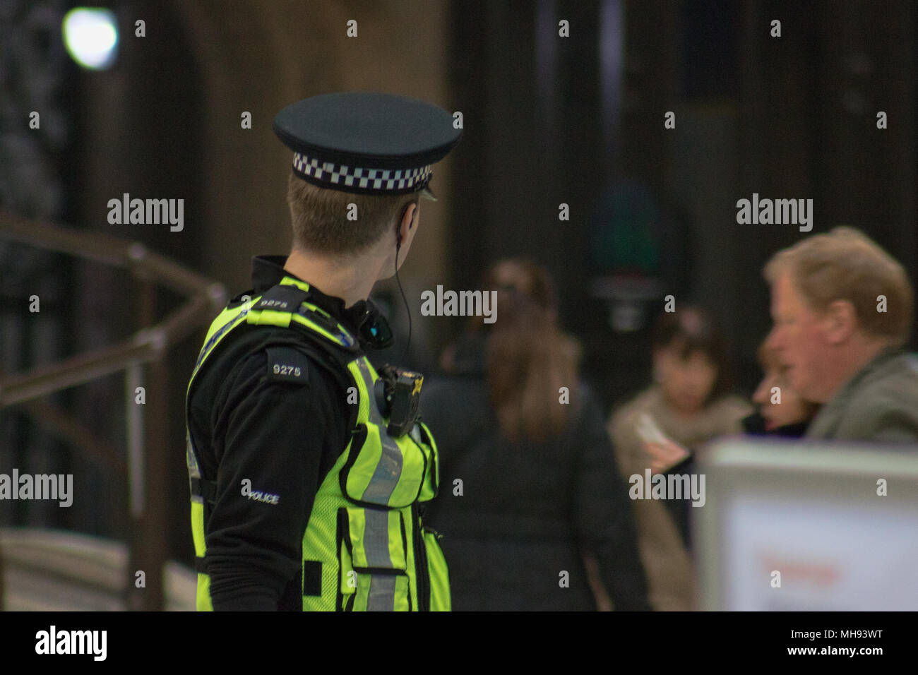 British Transport Police (BTP) officer patrols Glasgow Central train station, Glasgow, Scotland - Stock Image