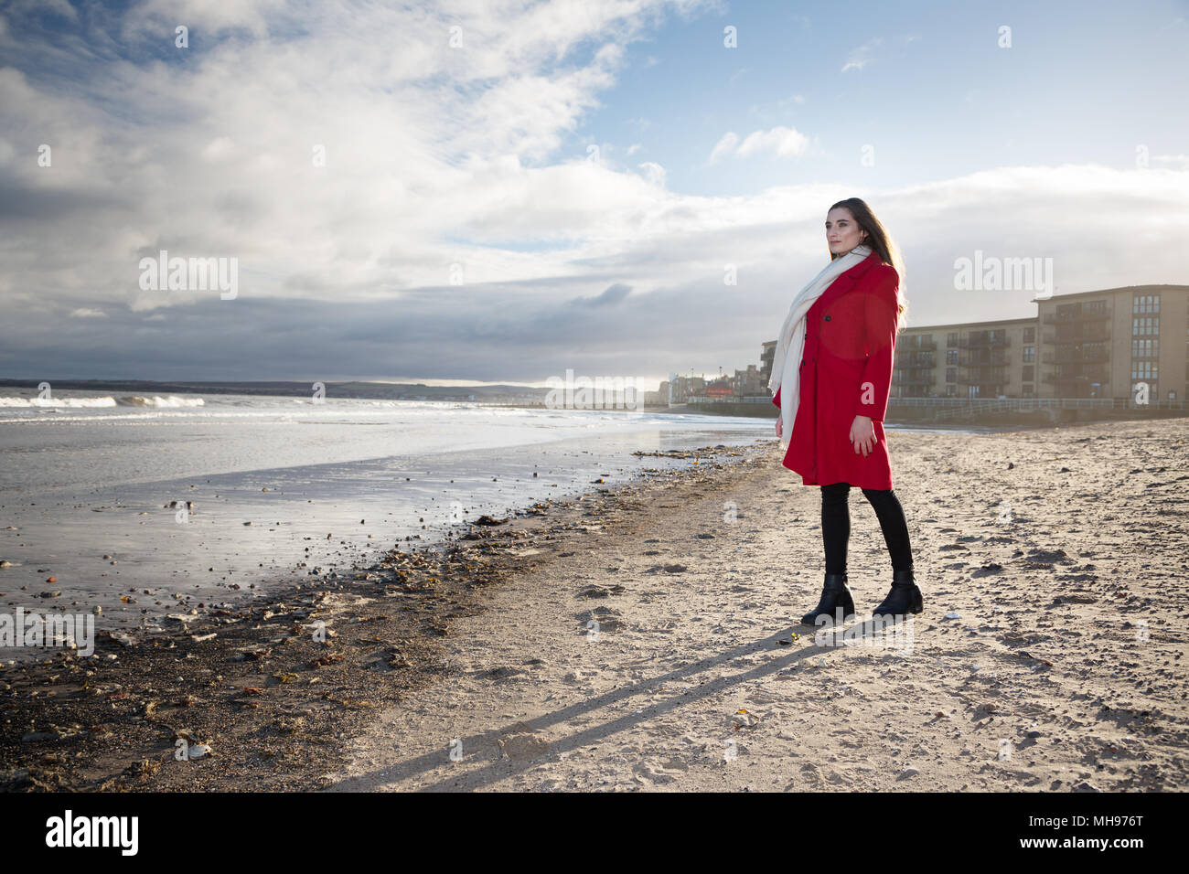 Woman at the beach, showing emotion and expression dealing with anxiety, grief, depression and mental health. - Stock Image