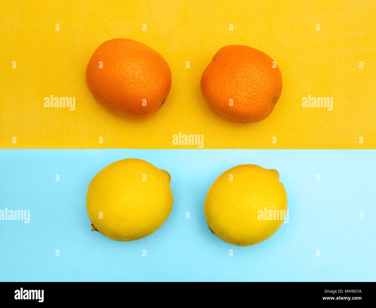 Two lemons and two tangerines are lying on two tone background Photo template in top view Stock Photo