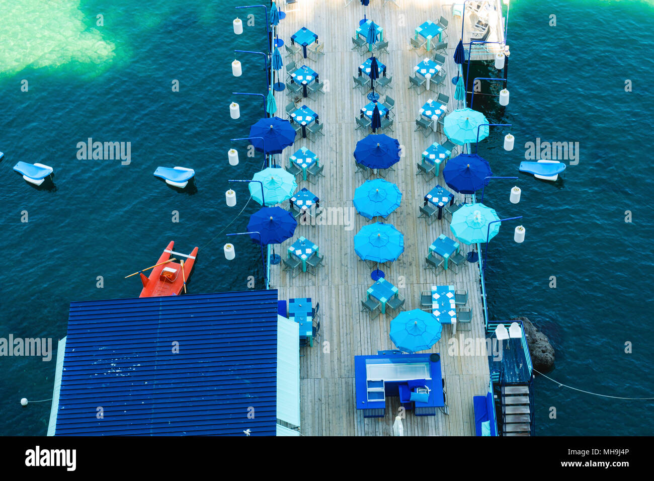 Blue umbrellas on the dock at Sorrento, Italy - Stock Image