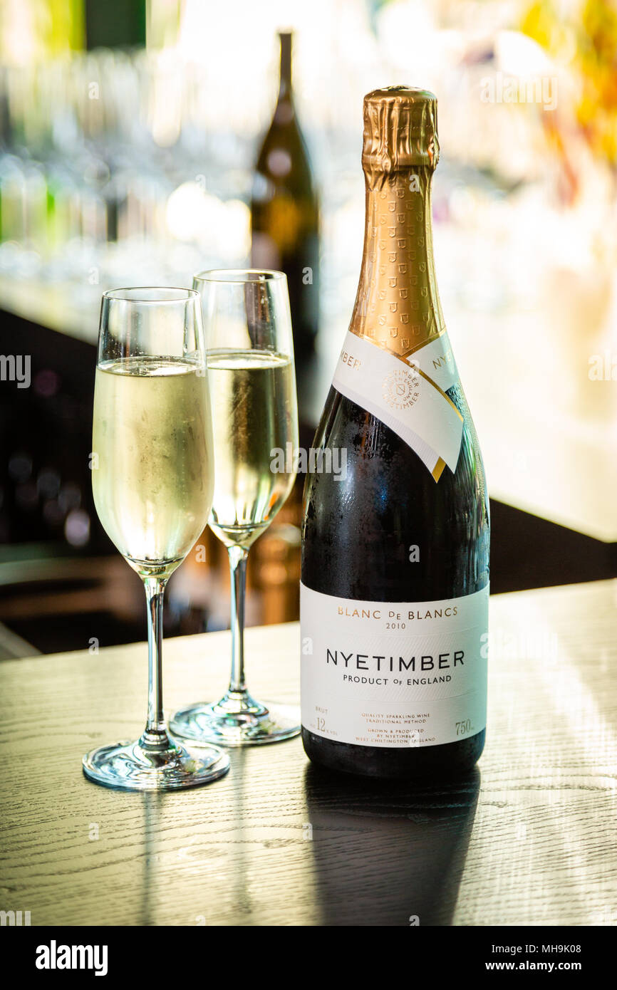 Nyetimber champagne bottle and two filled champagne flutes on a table, blurred background. - Stock Image