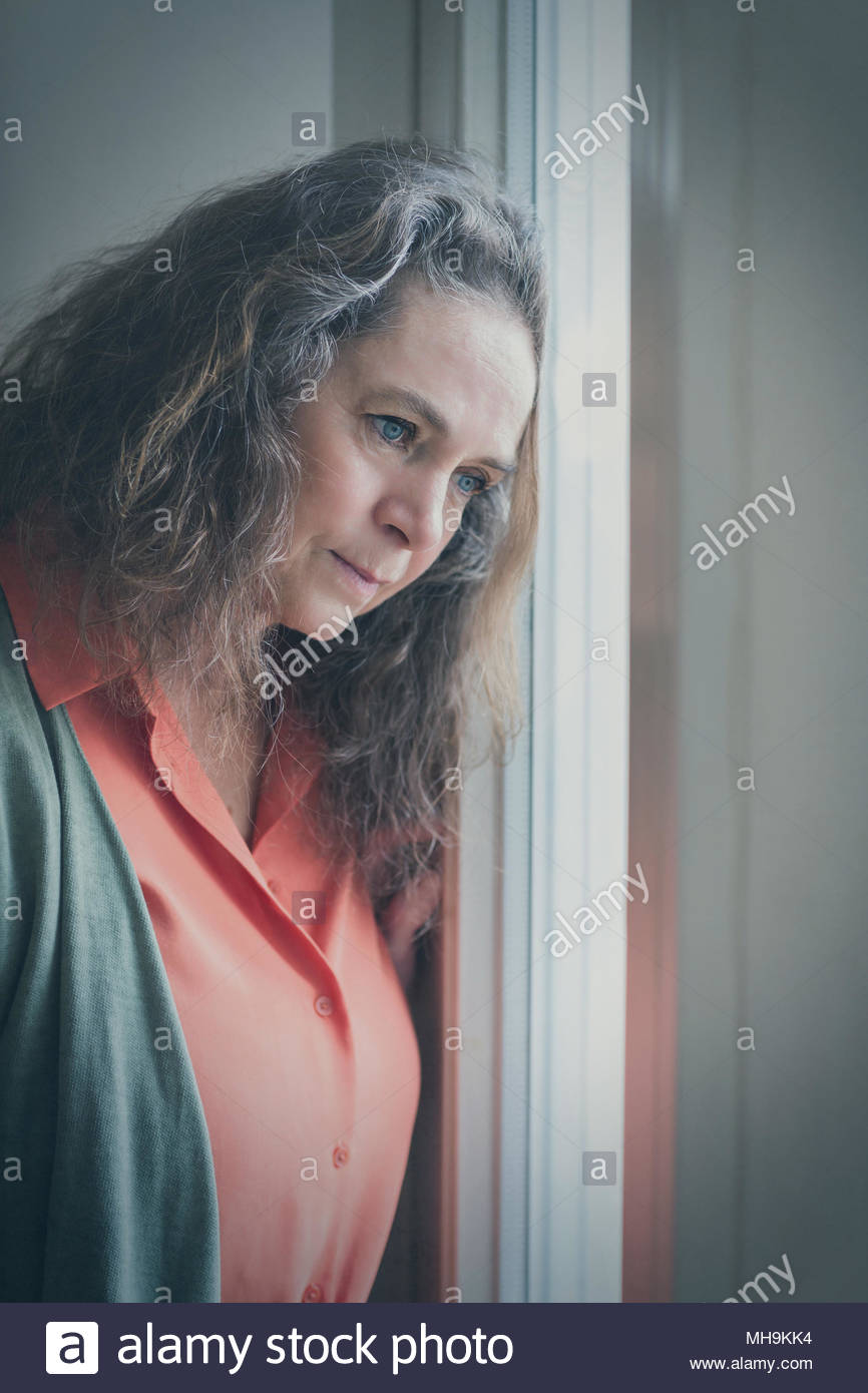 Thoughtful woman leaning her head on a window - Stock Image