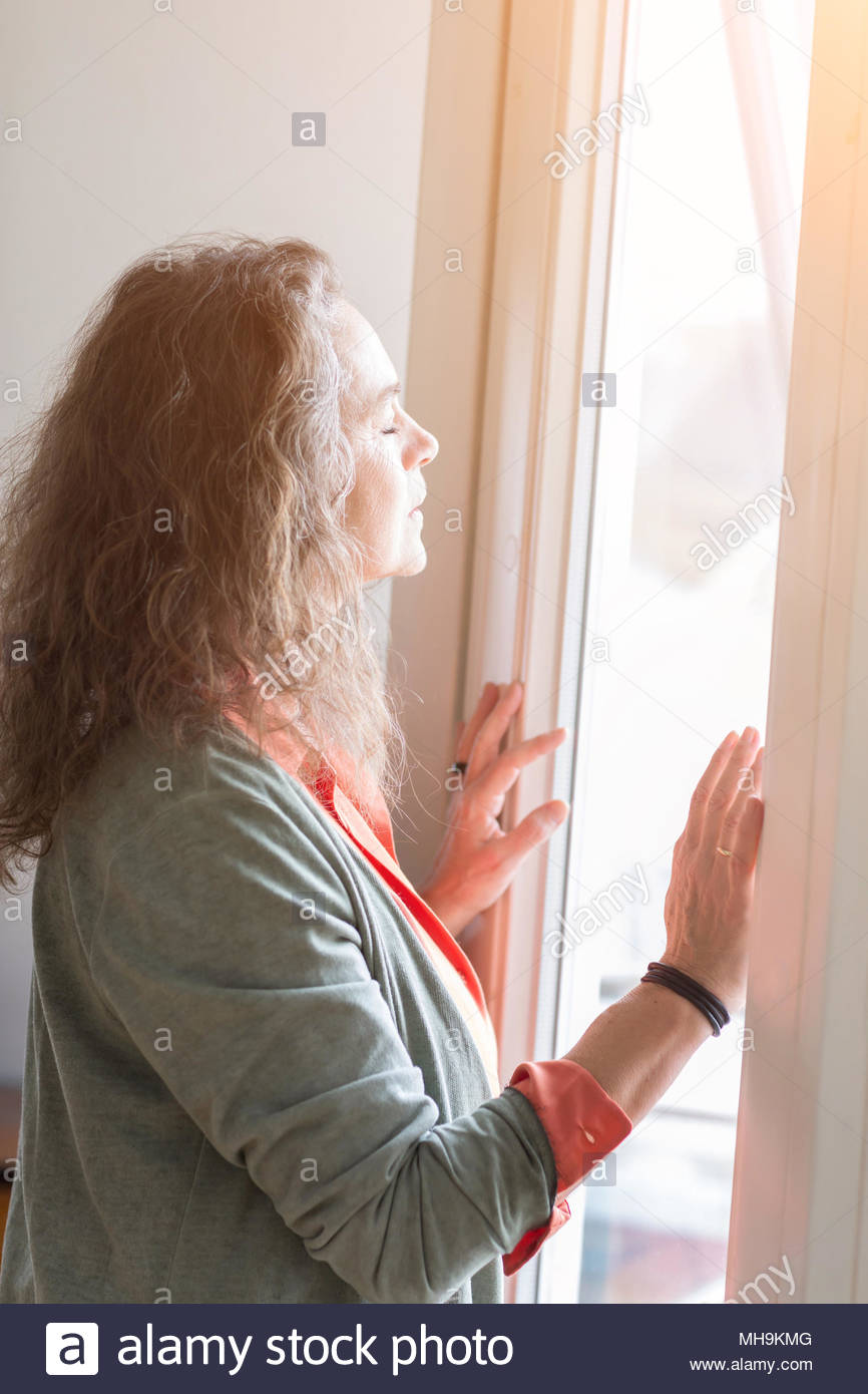 Attractive middle-aged woman enjoying the sunlight - Stock Image