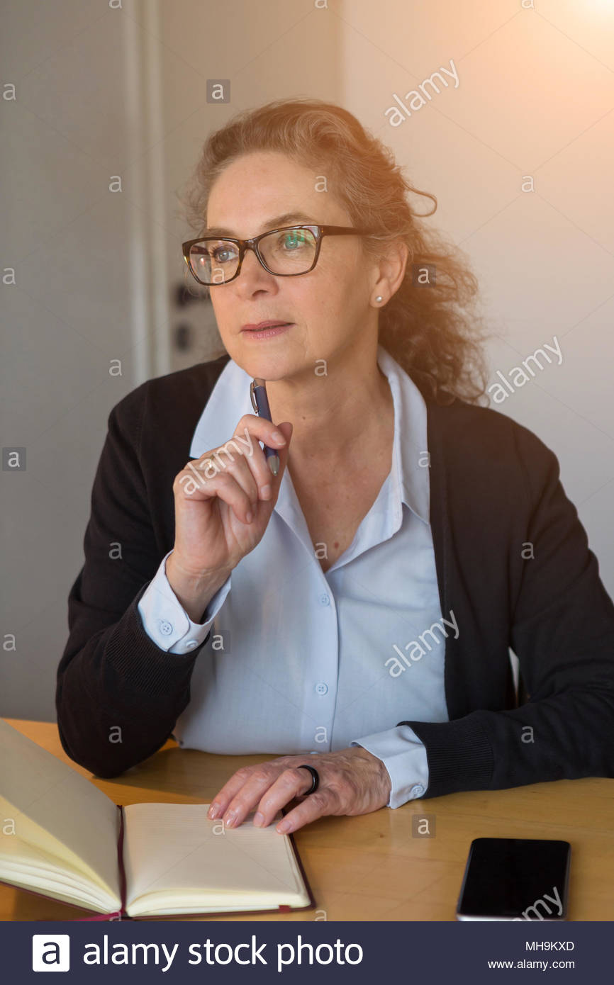 Thoughtful businesswoman working by lamplight - Stock Image