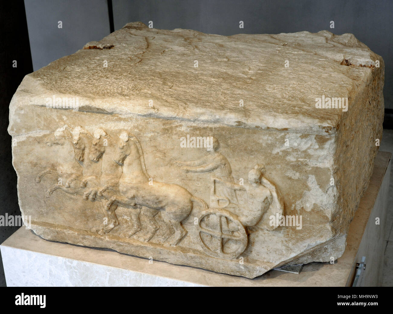 Base of a dedication. The relief depicts a scene from the apobates race. In the apobates race, the fully armed athlete jumped to the ground and then had to remount on the fast-moving chariot. Late 4th-Early 3rd century BC. Acropolis Museum. Athens. Greece. - Stock Image