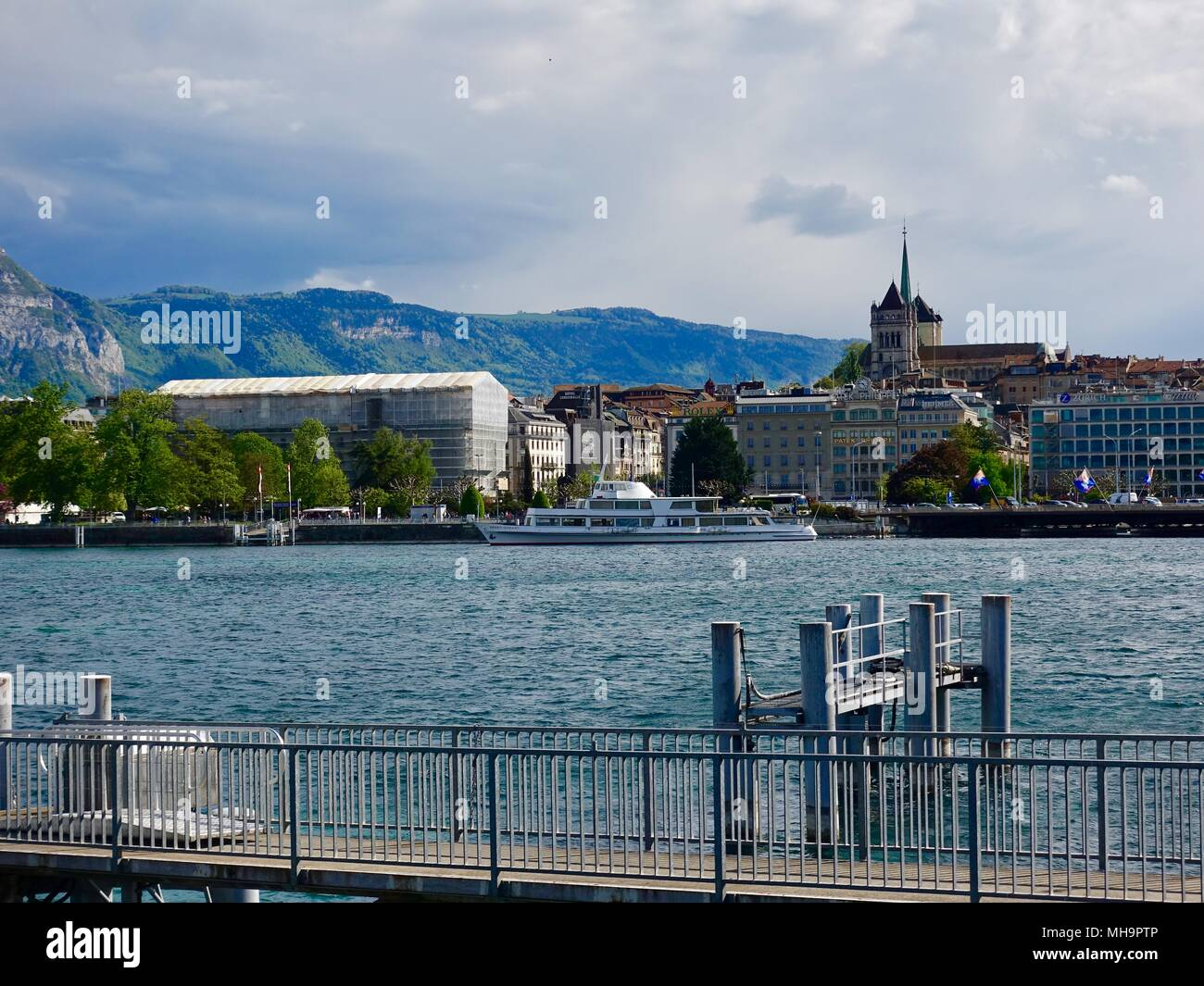 Looking across Lake Geneva, Lac Léman, towards St. Peter's Cathedral, Saint Pierre Cathedral, and cloud-topped mountains Geneva, Switzerland. - Stock Image