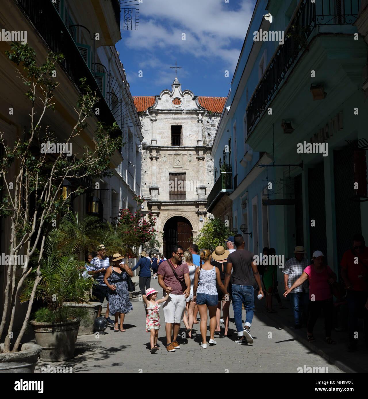 Tourists walk down Teniente Rey street in the historic neighborhood of Havana Vieja in Havana, Cuba. - Stock Image