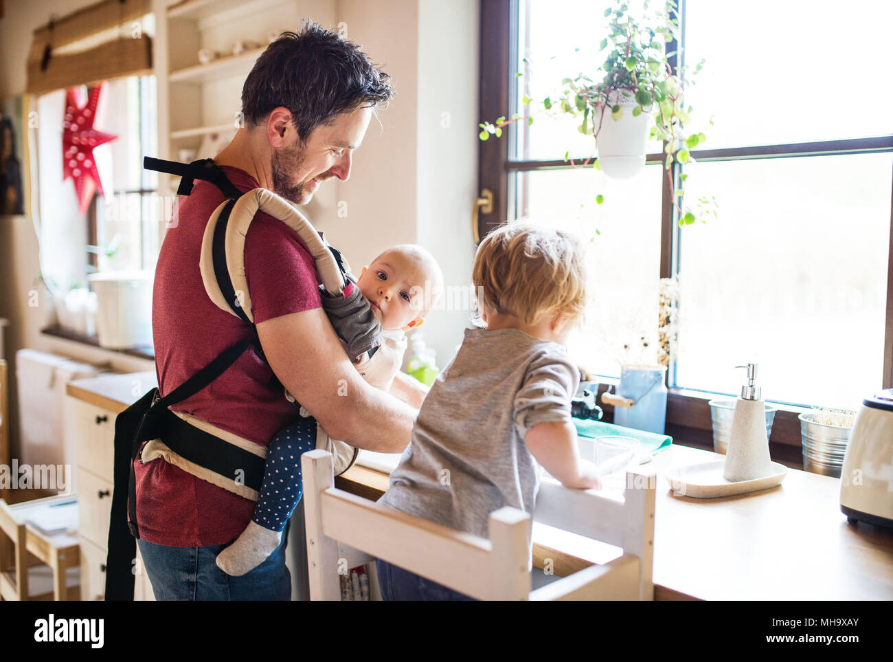 Father and two toddlers washing up the dishes. - Stock Image