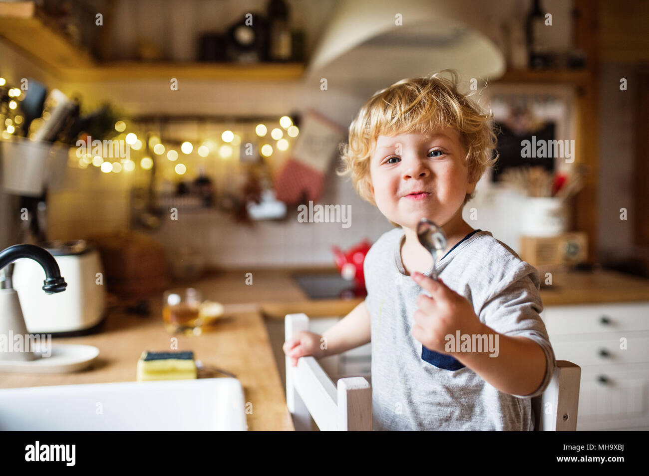 A toddler boy washing up the dishes. - Stock Image