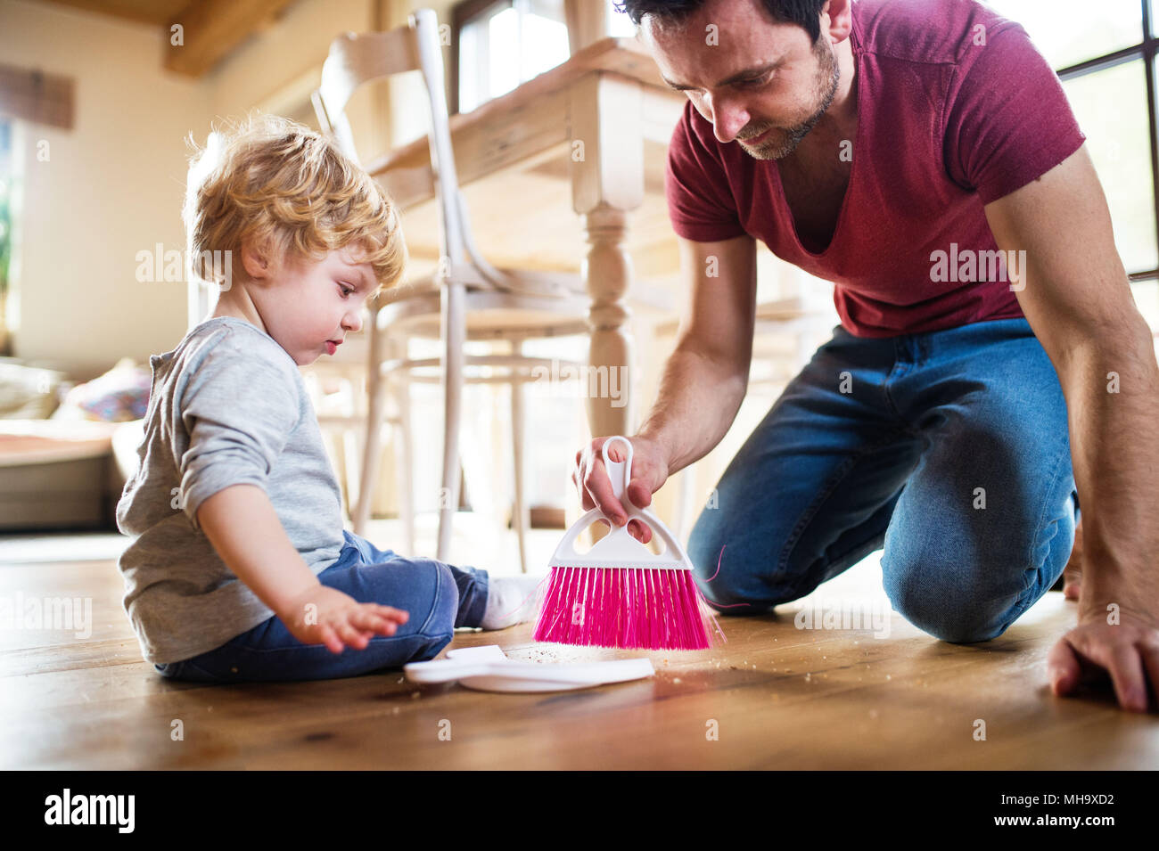 Handsome father and toddler boy with brush and dustpan. - Stock Image