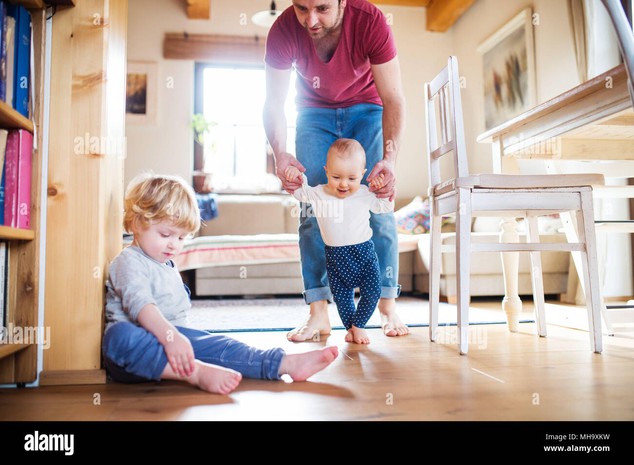 Father with two toddlers at home. First steps. - Stock Image