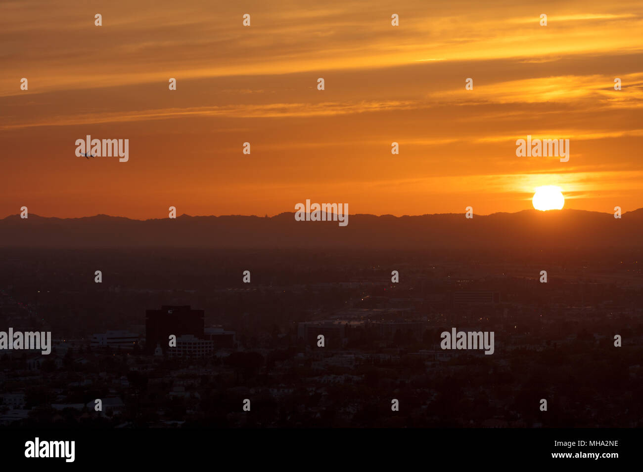 Jetliner taking off at sunset - Stock Image