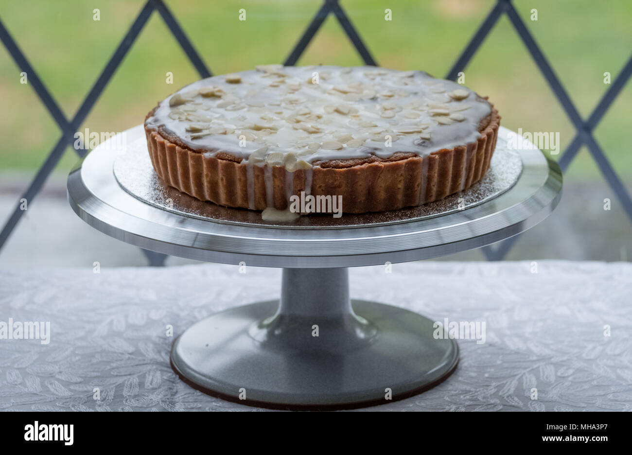 Home baked Bakewell Tart cake on metal cake stand in front of window, with garden behind. - Stock Image