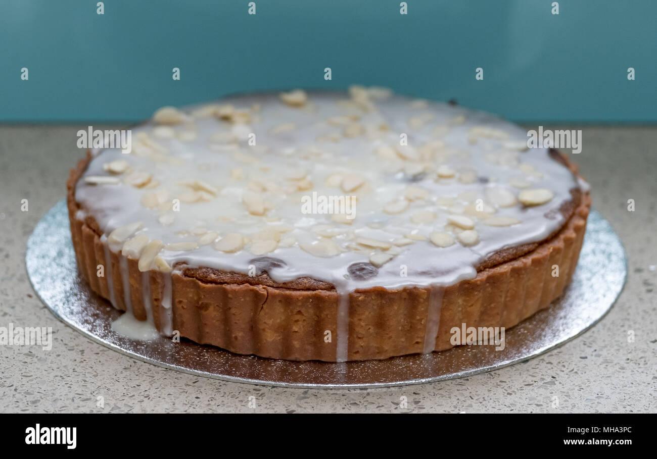Home baked Bakewell tart cake on foil platter against aqua blue background - Stock Image
