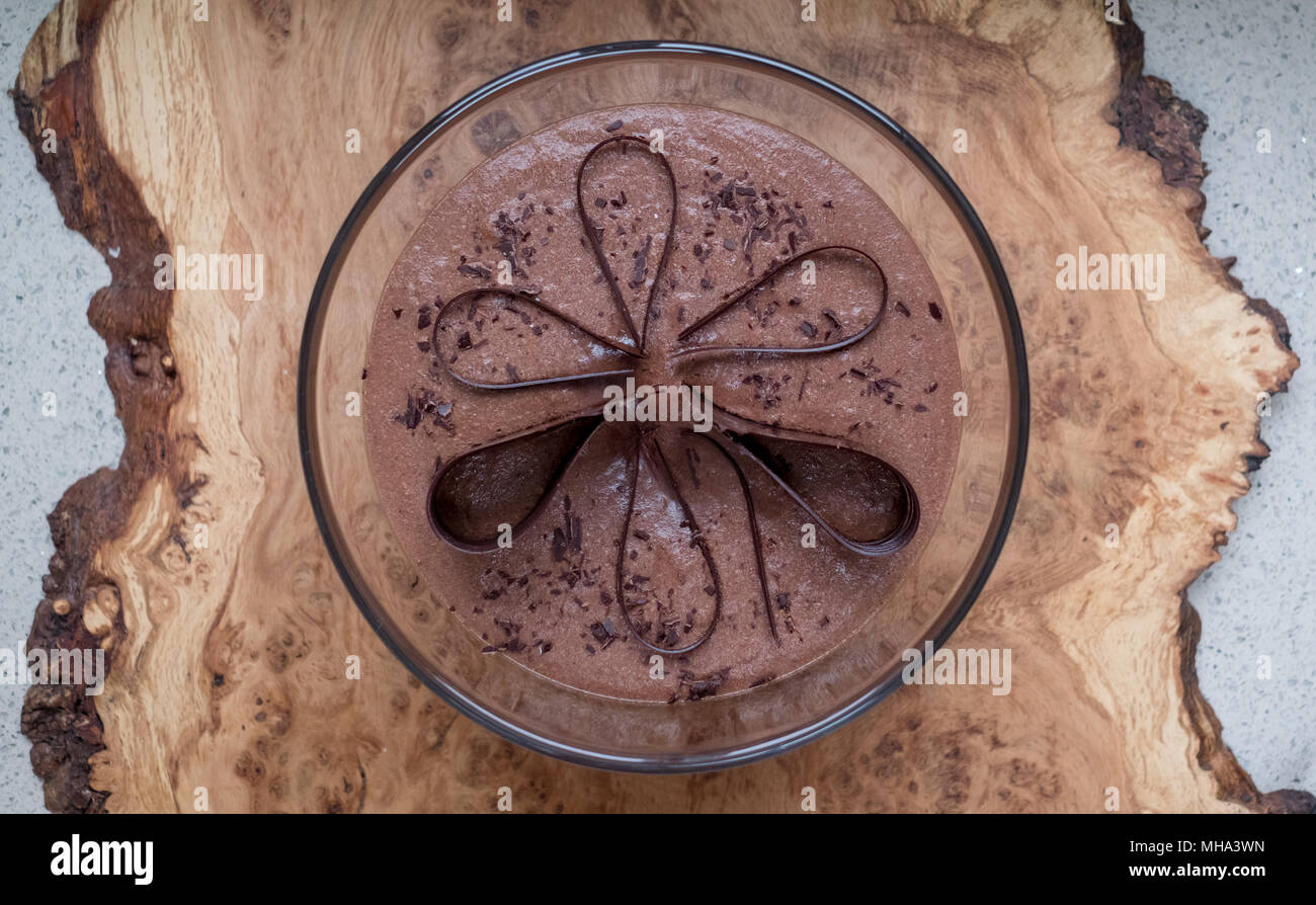 Glass bowl with chocolate mousse standing on an olive wood platter, decorated with chocolate shavings and curls. - Stock Image