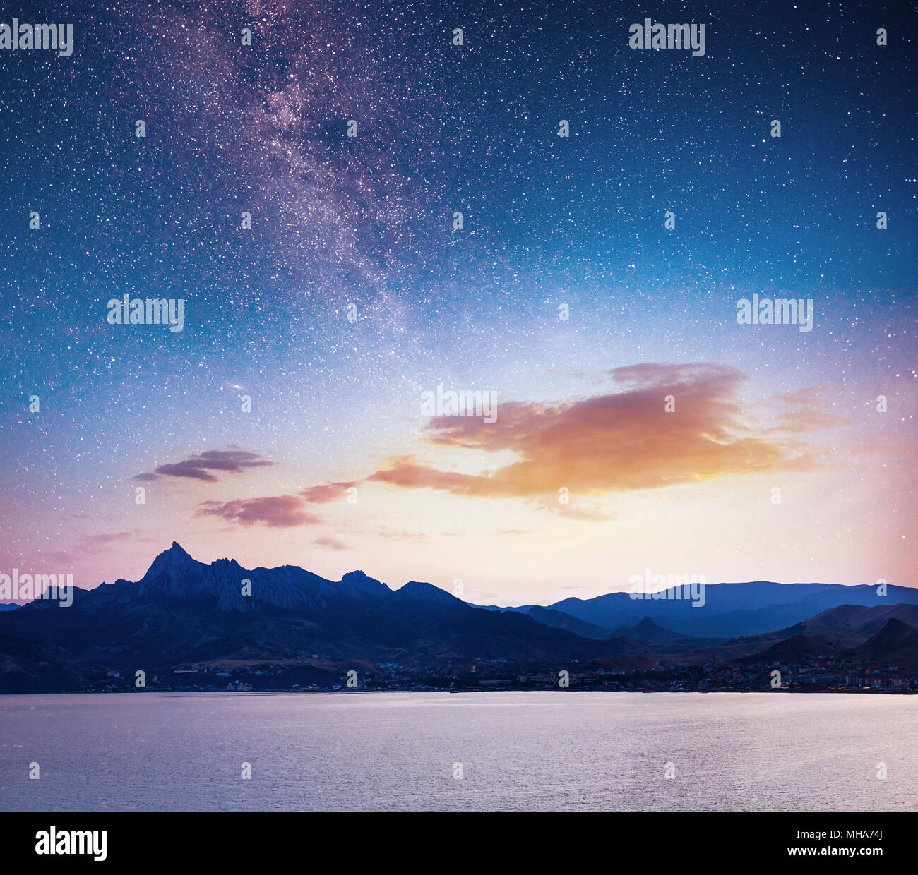 magnificent panorama of sunrise over the sea. Vibrant night sky with stars and nebula and galaxy. Deep sky astrophoto Stock Photo