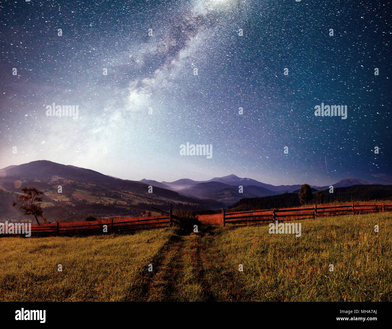 Mountain summer landscape. High grass and vibrant night sky with stars and nebula and galaxy. Deep sky astrophoto Stock Photo