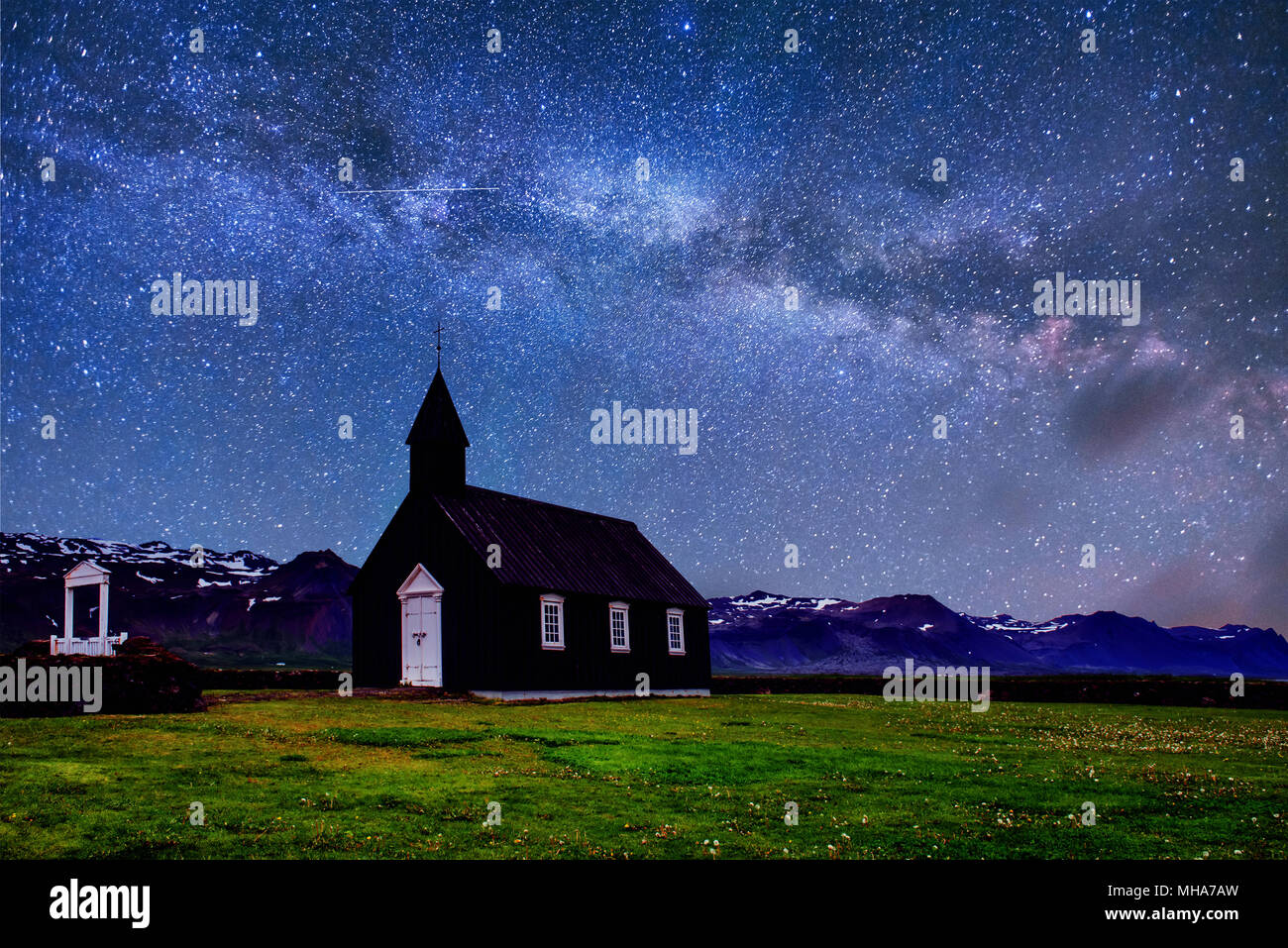 Mountain View Iceland. Fantastic starry sky and the milky way. Beautiful black wooden church in Budir - Stock Image