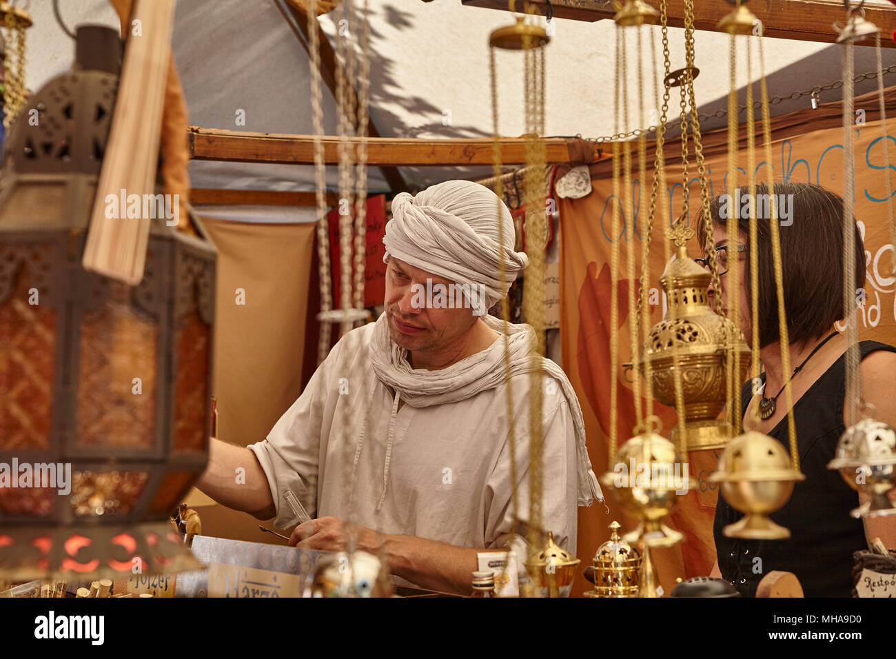 Medieval Dealer Selling Incense and Myrrh with Ornaments in the Foreground - Stock Image