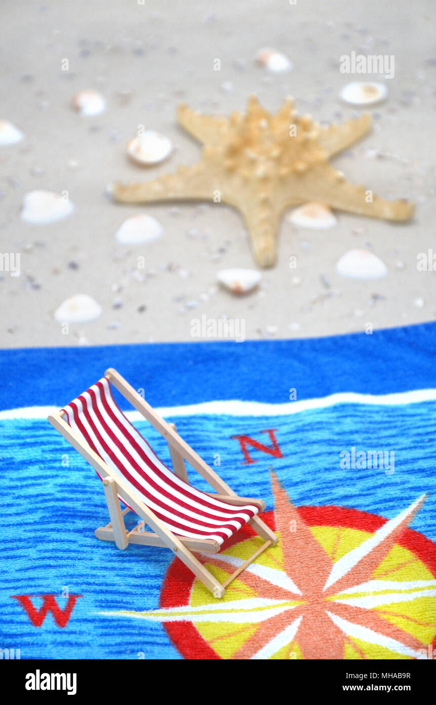 Towel On The Beach With A Starfish, Shells, And A Chair