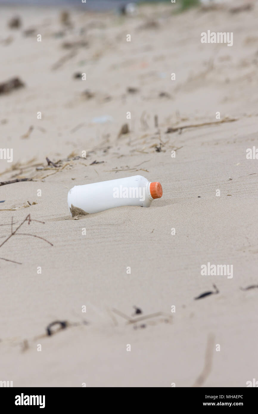 Plastic drink bottle washed up on a sandy beach an example of the many pieces of garbage in the sea around the world - Stock Image