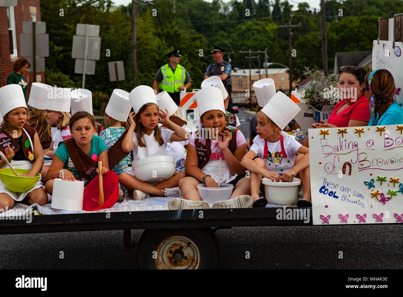 Mountville, PA, USA - May 30, 2012:  A Girl Scout Brownies Troop using bowls to make brownies ride on a trailer in the annual old-fashioned, small tow - Stock Image