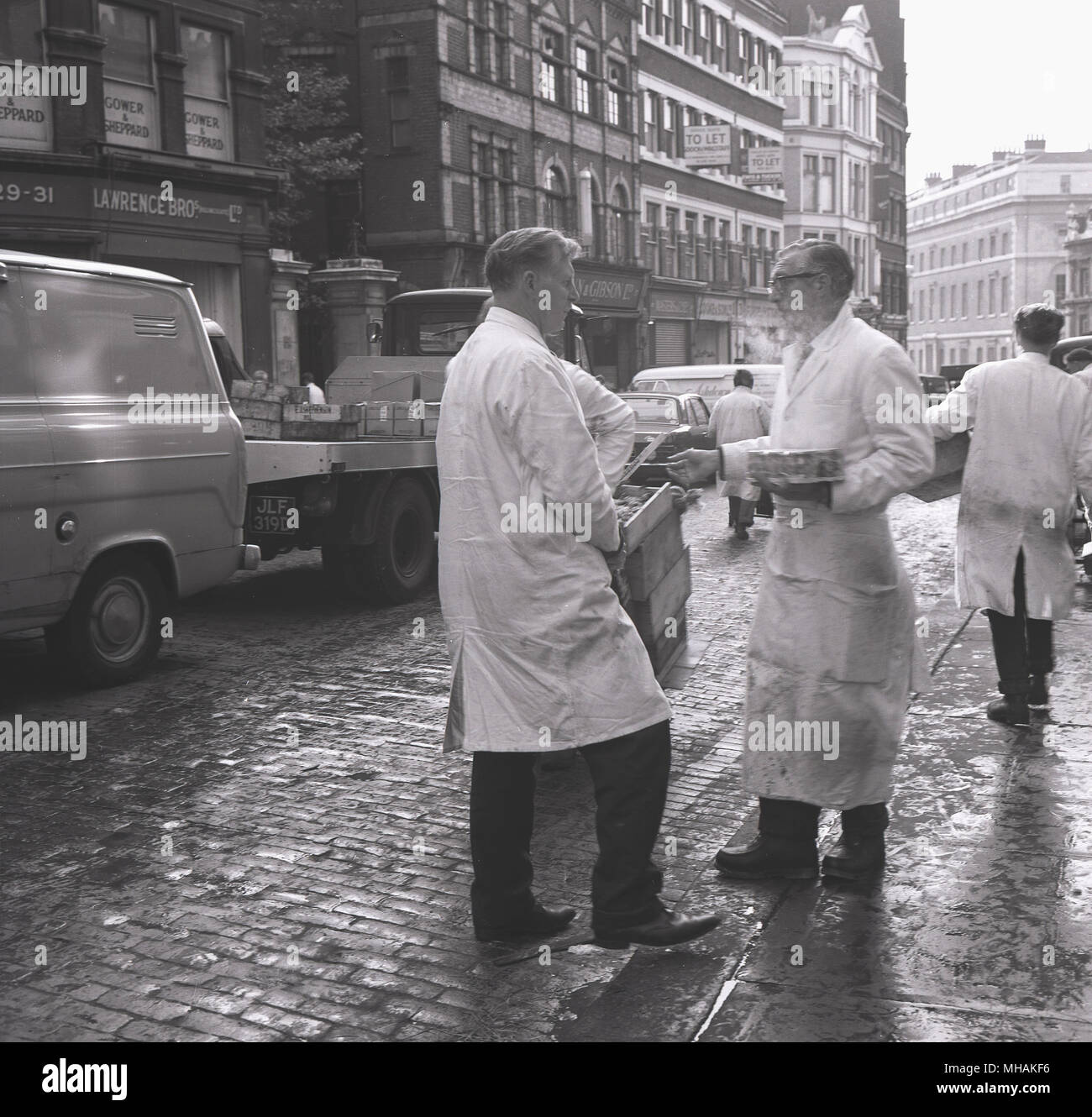 1950s, historical, two fish merchants in overalls stand chatting on a cobbled street outside the Billingsgate wholesale fish market, Lonond, England, UK. - Stock Image