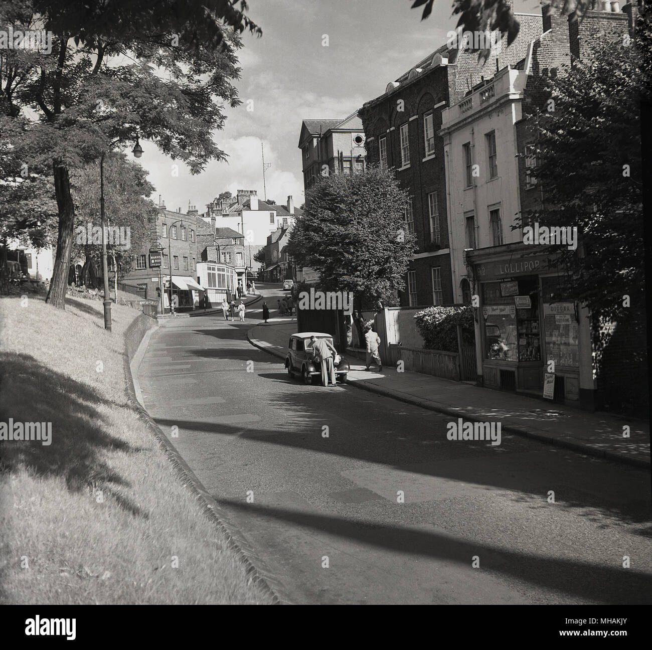 1950s, historical picture of a quiet post-war Hampstead high street. This picture by J Allan Cash was most likely taken on a s Sunday morning as there no motorcars on the road, apart from one parked car. No 92 is a newsagent's 'Lollipop', selling tobacco such as 'Gold Flake'. Hampstead was a pretty leafy village in this era and is now promoted as the 'orginal urban village'. - Stock Image