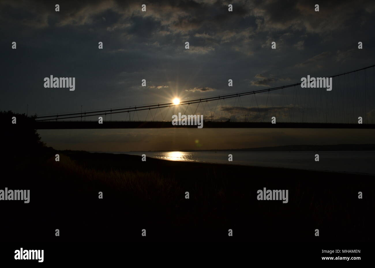 An image showing the humber bridge with the sun dawning in the distance - Stock Image