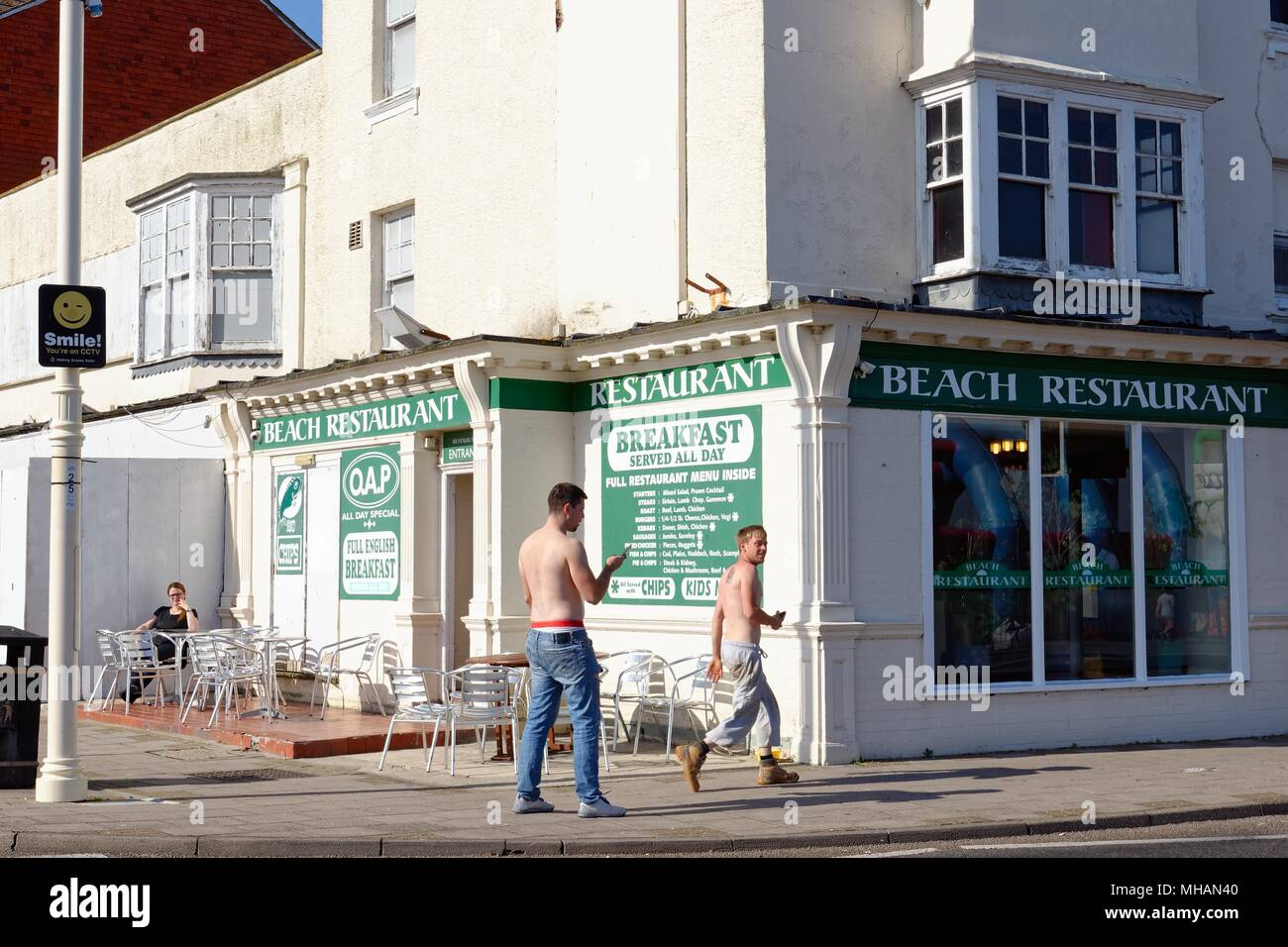 Two bare chested youths, one on mobile phone walking past seafront cafe with lady sitting outside, in Bognor Regis West Sussex England UK - Stock Image