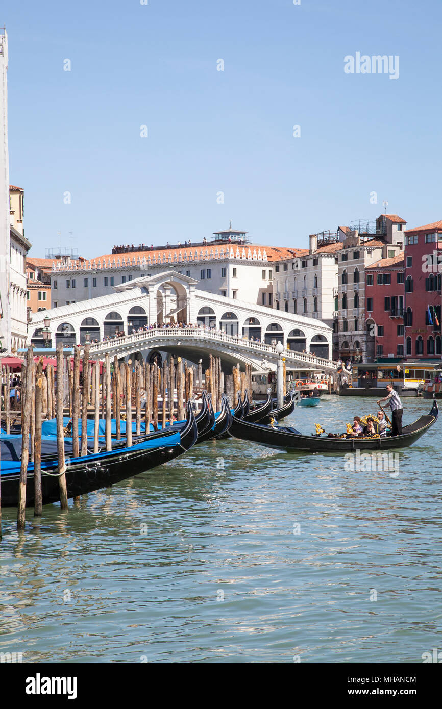 Gondolas in front of Rialto bridge, on the Grand Canal,  Venice, Veneto, Italy with a golndolier returning his boat to its mooring and tourists on the - Stock Image
