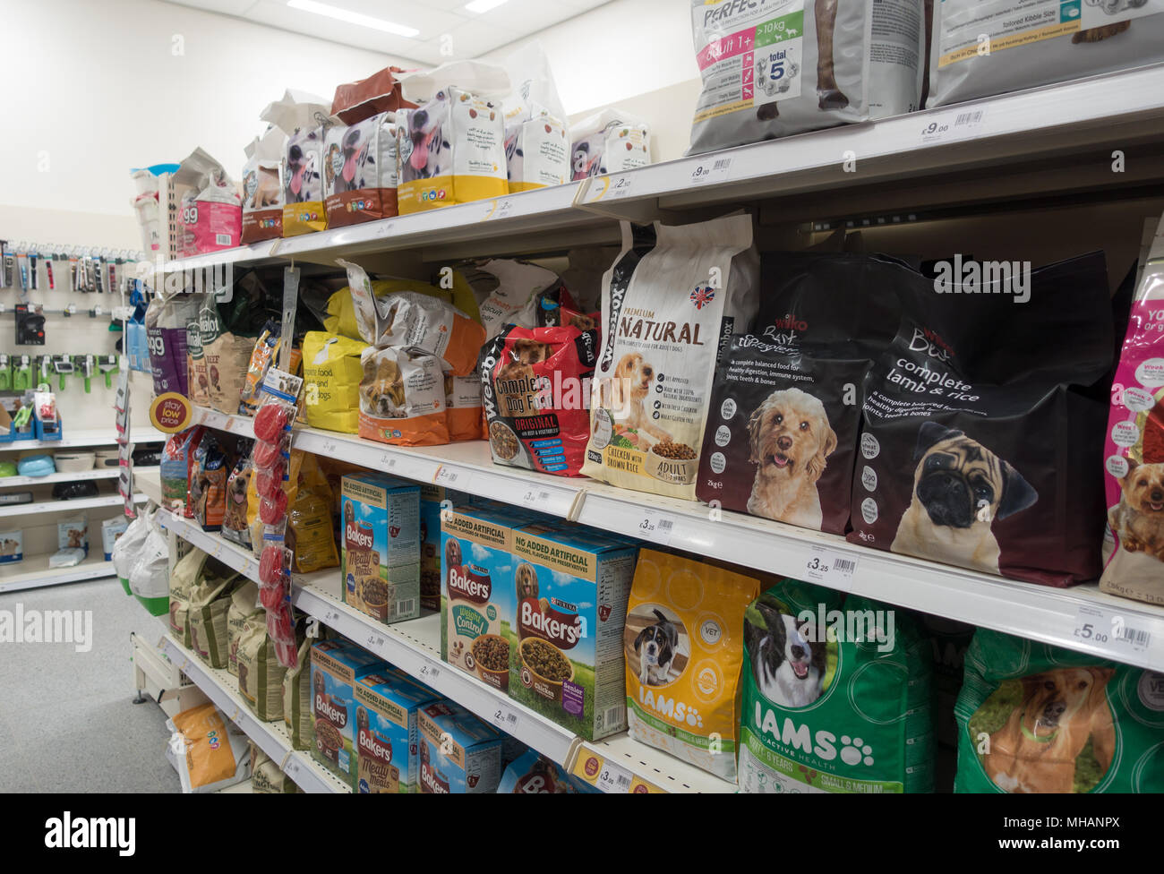 Many different brands of dog food on a shelf in a shop - Stock Image