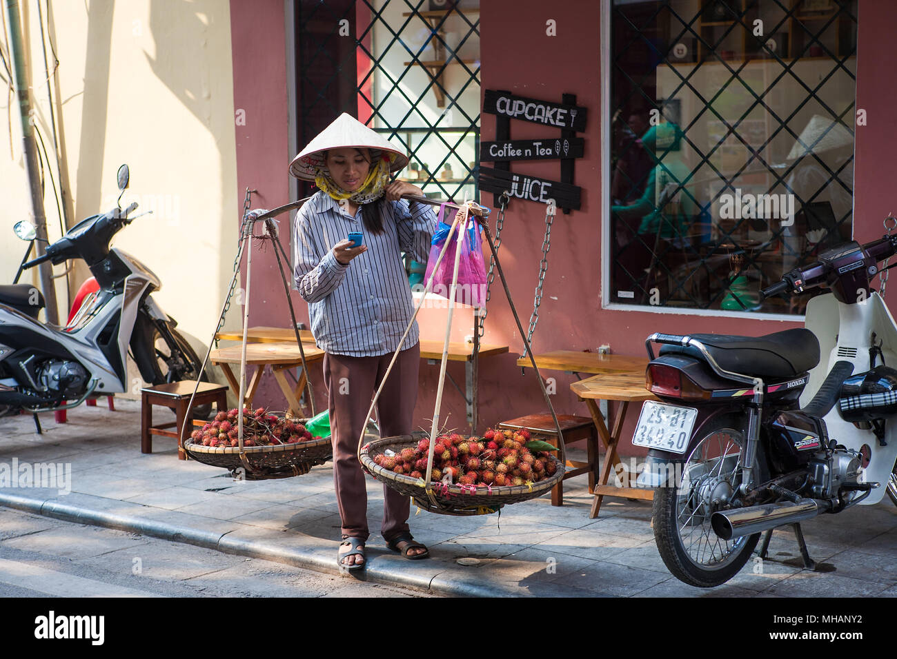 Traditional street-seller with yoke baskets, leaf-hat and mobile phone, Mã Mây, Hoàn Kiếm, Hà Nội, Vietnam - Stock Image