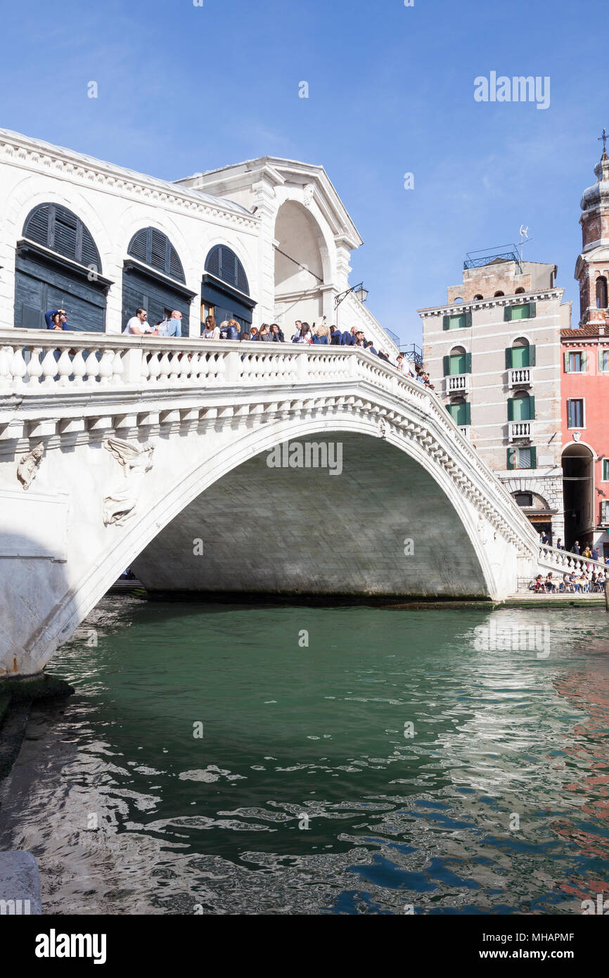 Rialto Bridge with tourists, Grand Canal, Venice, Veneto, Italy in a close up view with reflection on the water - Stock Image