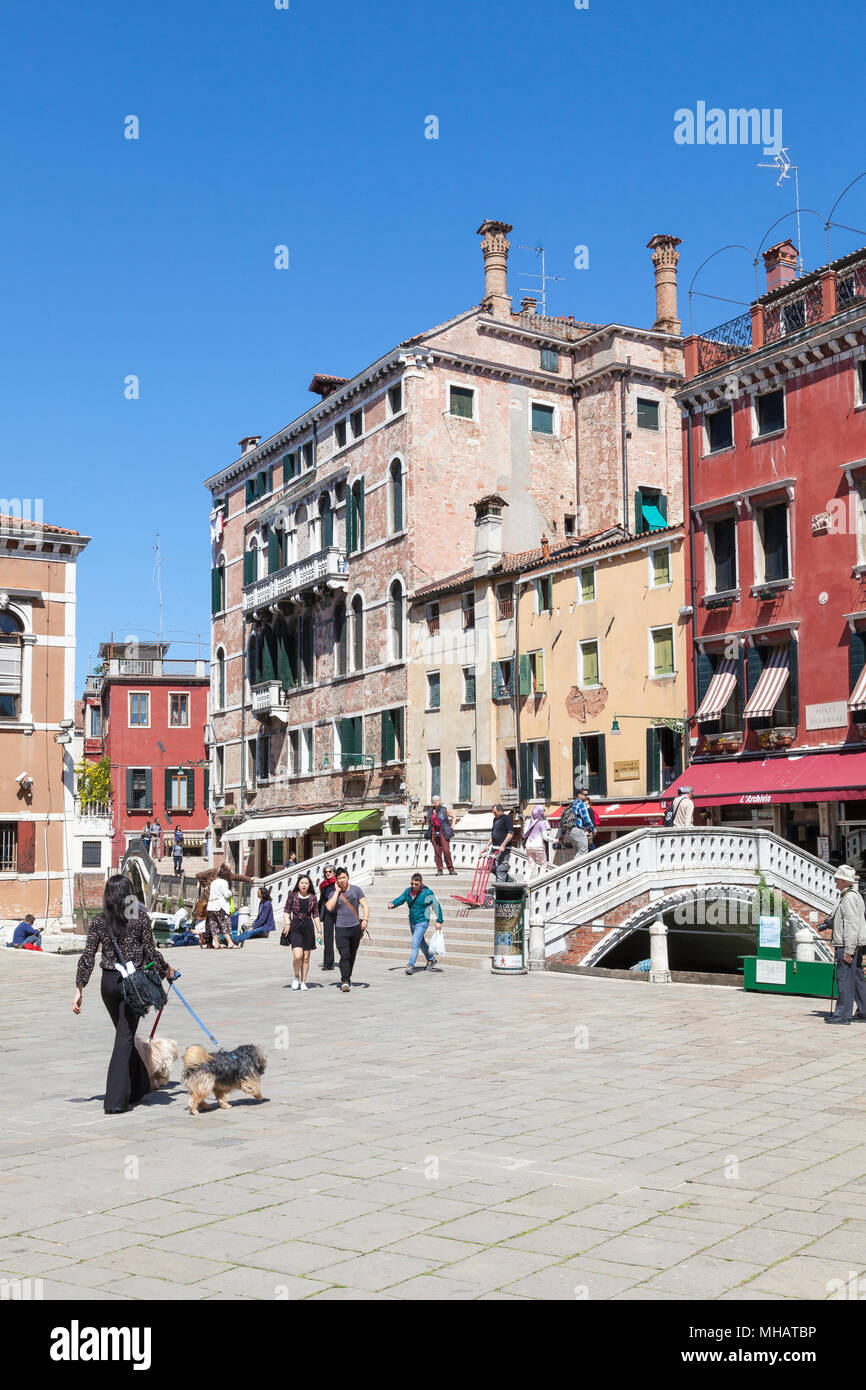 Colorful buildings and bridge on Campo dei Frari, San Polo, Venice, Veneto, Italy with a local woman walking her dogs and tourists - Stock Image