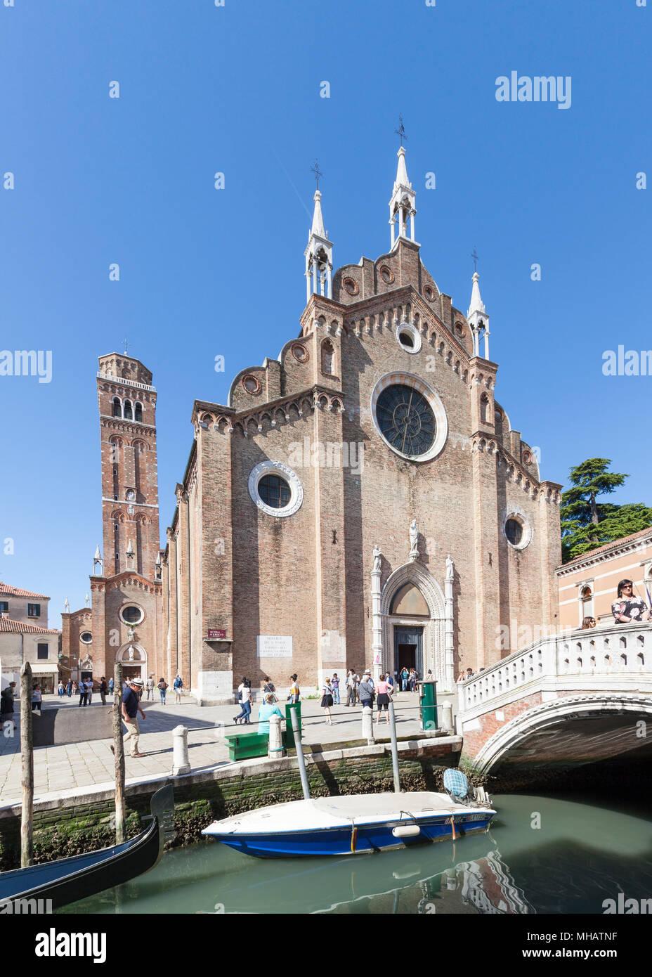Basilica di Santa Maria Gloriosa dei Frari, Campo dei Frari, San Polo, Venice, Veneto, Italy with reflections and a boat in the canal. Tourists in cam - Stock Image