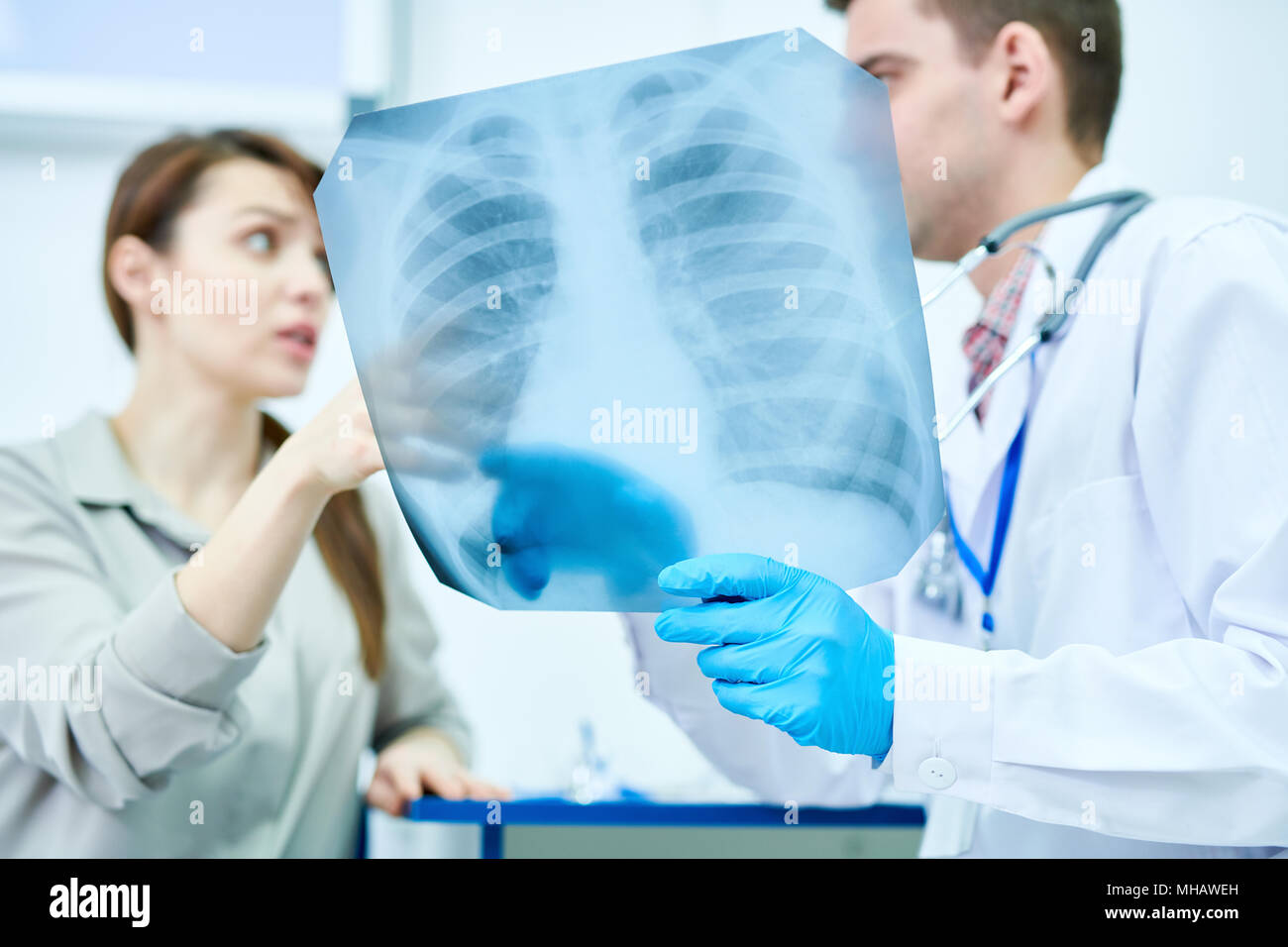 Waist up portrait of doctor holding chest x-ray explaining in to female patient, copy space - Stock Image